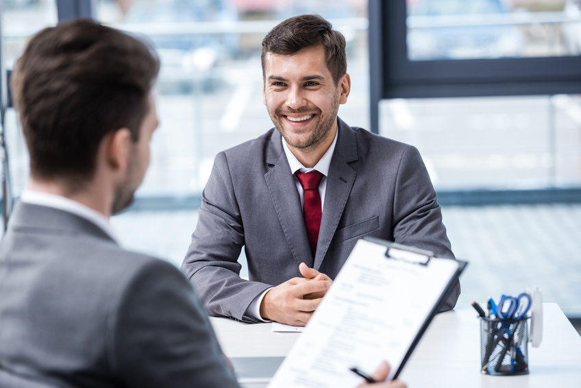 Smiling young businessman looking at manager with clipboard at job interview